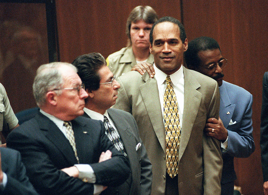Attorney Johnnie Cochran Jr. holds onto O.J. Simpson as the not guilty verdict is read in a Los Angeles courtroom Tuesday morning, Oct. 3, 1995. Left is F. Lee Bailey and second from left is Robert Kardashian. (AP Photo/Pool, Myung J. Chun)