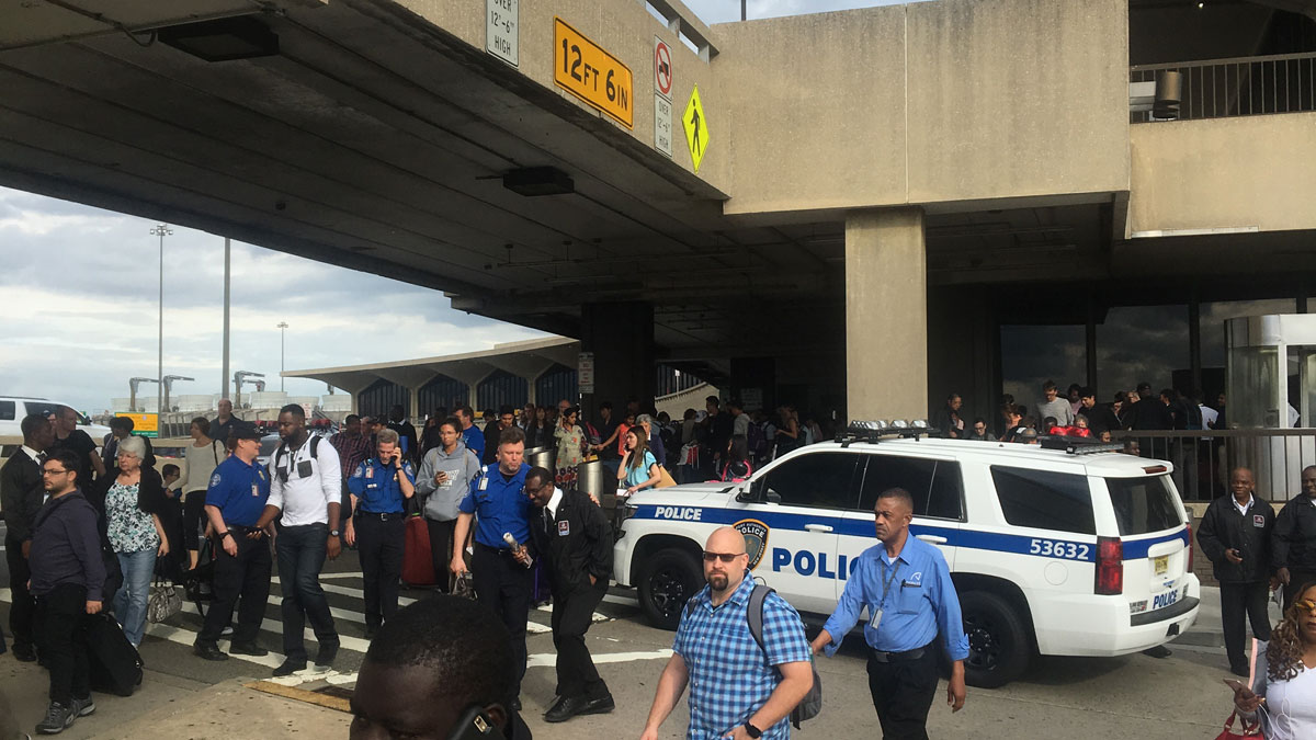 Passengers and a police vehicle outside Newark Airport after a terminal was evacuated.