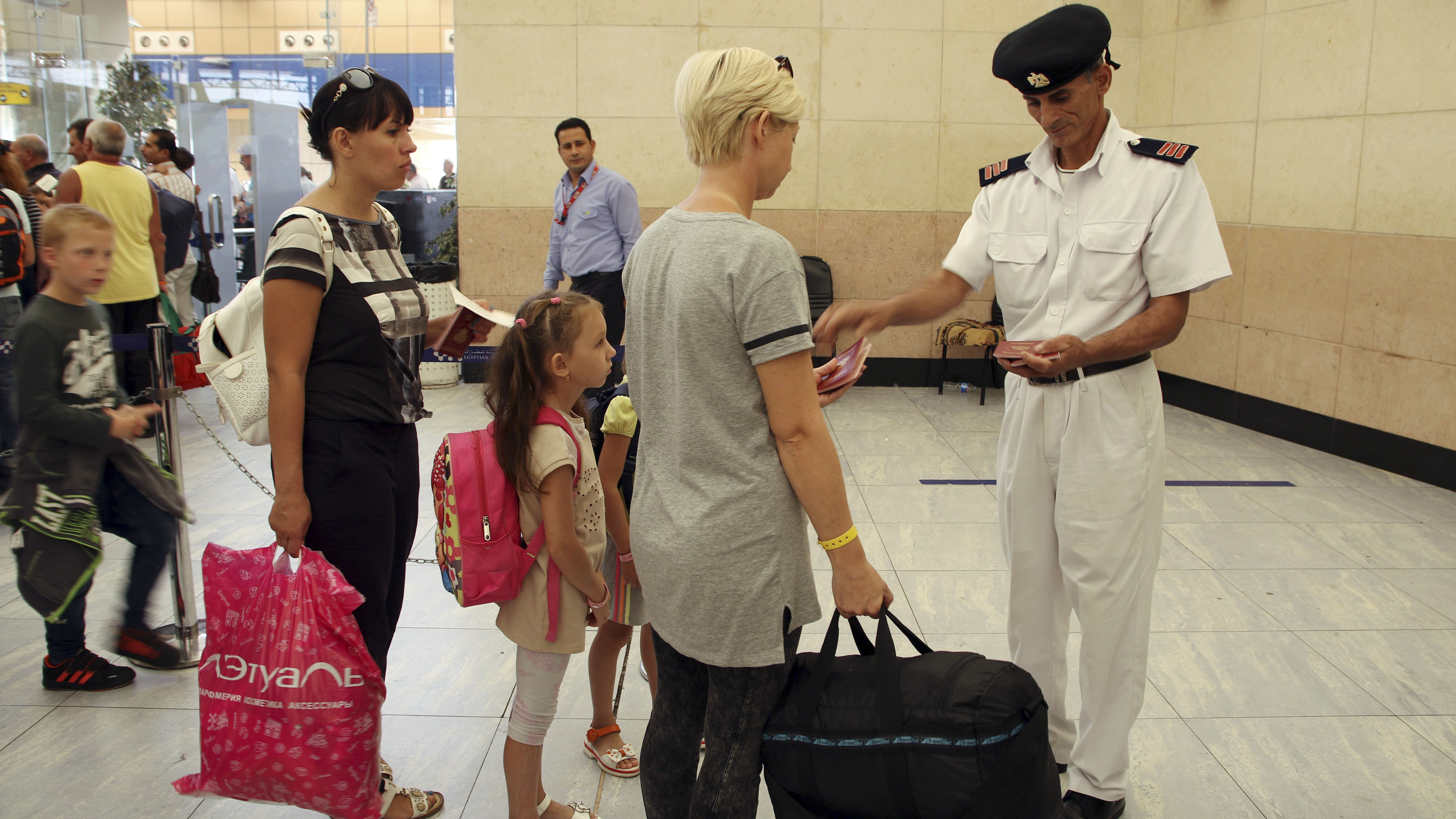 Tourists have their documents checked by Egyptian police as they prepare to be evacuated from Sharm el-Sheikh airport, south Sinai, Egypt, Friday, Nov. 6, 2015. Egyptian police carried out detailed security checks on Friday at the airport in Sharm el-Sheikh, the resort from where the doomed Russian plane took off last weekend, after U.K. officials confirmed that flights will start bringing stranded British tourists home from the Sinai Peninsula.