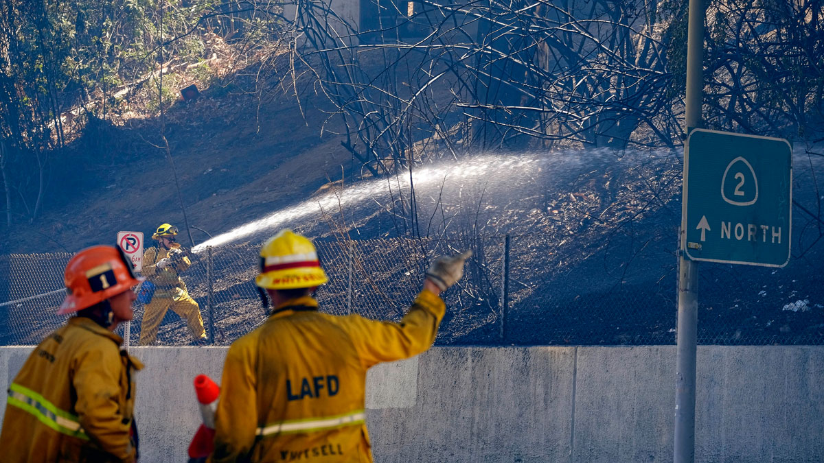 Firefighters douse a hillside under State Route 2 after a brush fire swept through threatening homes in Los Angeles on June 19, 2016. Los Angeles firefighters say they have contained the fire in the densely populated neighborhood along a freeway. Intense heat could hamper efforts to fight fires across three states. In Arizona, officials say the heat was responsible for two deaths Sunday.