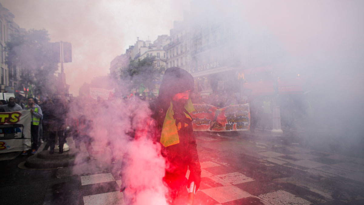 A man holds a flare at a demonstration of labor union members on strike against the French government and labor law reforms in Paris, Thursday, June 2, 2016. Workers are on strike at nearly all of France's nuclear plants and on the national rail service as part of months of protests over changes to labor protections.