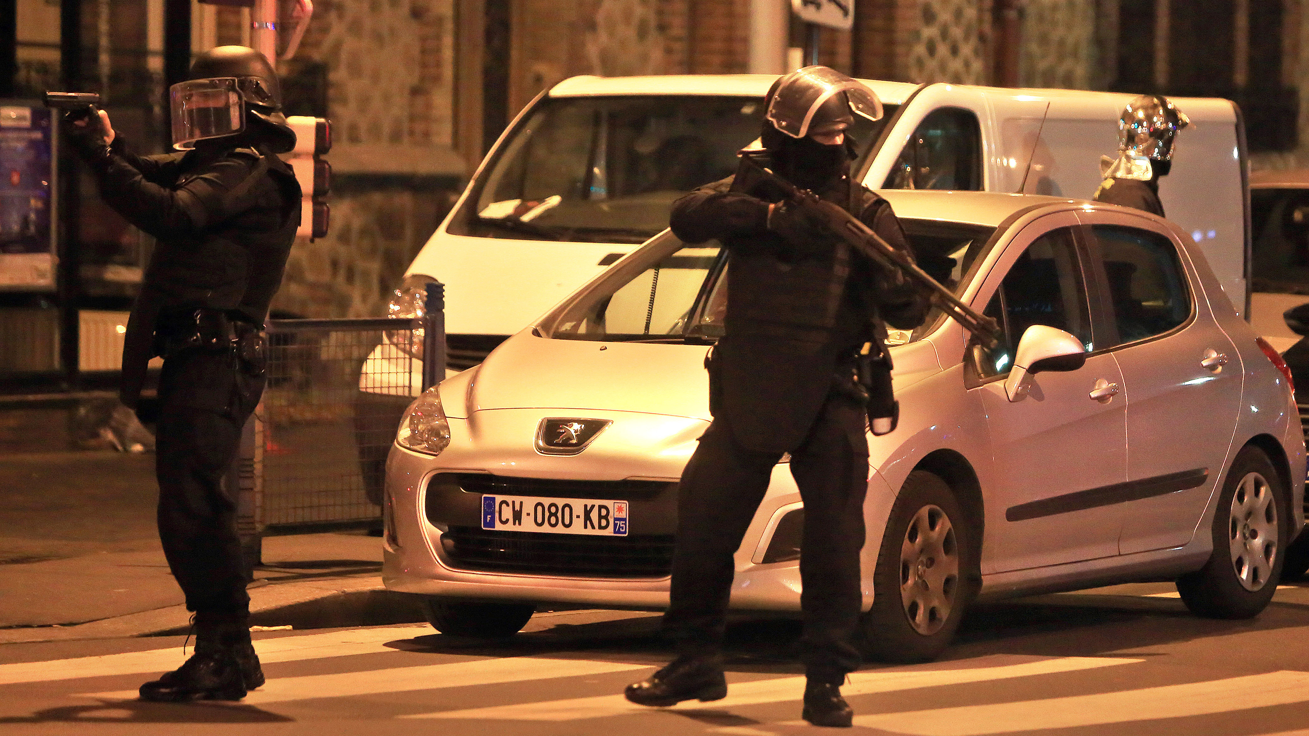 Police officers take up positions in Saint Denis, a northern suburb of Paris, Wednesday, Nov. 18, 2015. Authorities in the Paris suburb of Saint Denis are telling residents to stay inside during a large police operation near France's national stadium that two officials say is linked to last week's deadly attacks.