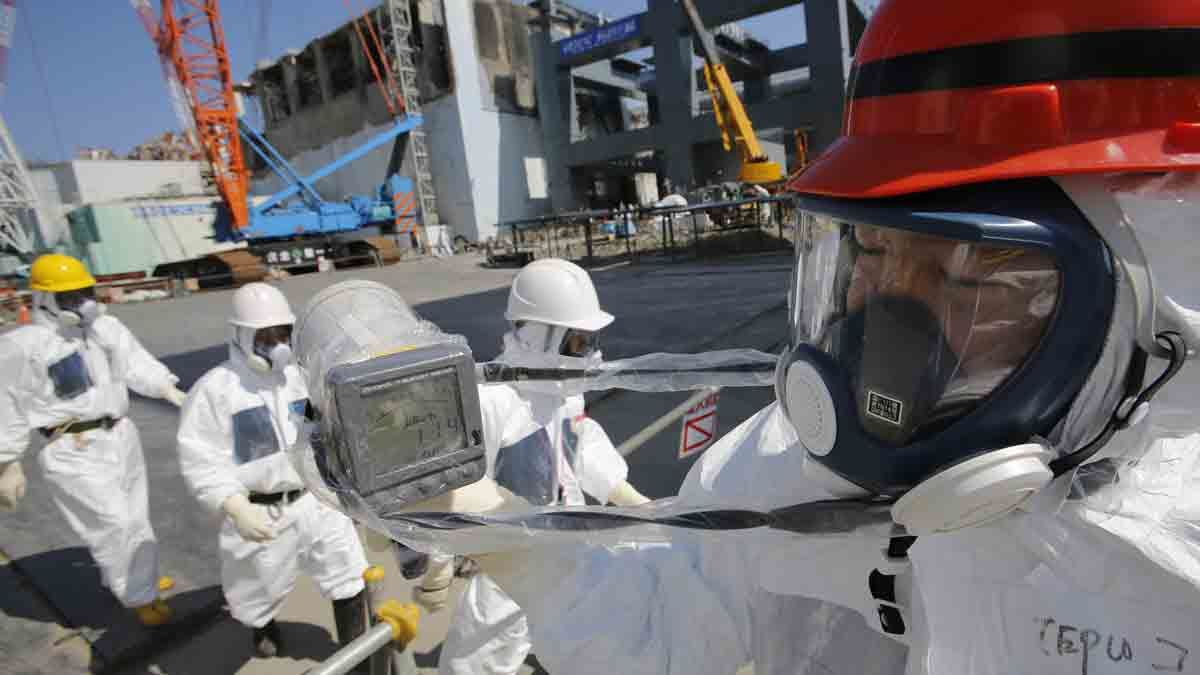 File Photo: A radiation monitor reads 114.00 microsieverts per hour as members of the media and Tokyo Electric Power Co. (Tepco) employees, wearing protective suits and masks, visit the No. 4 reactor building, background center, and the construction of a storage unit for melted fuel rods, background right, at the company's Fukushima Dai-Ichi nuclear power plant in Okuma, Fukushima Prefecture, Japan, on March 6, 2013.
