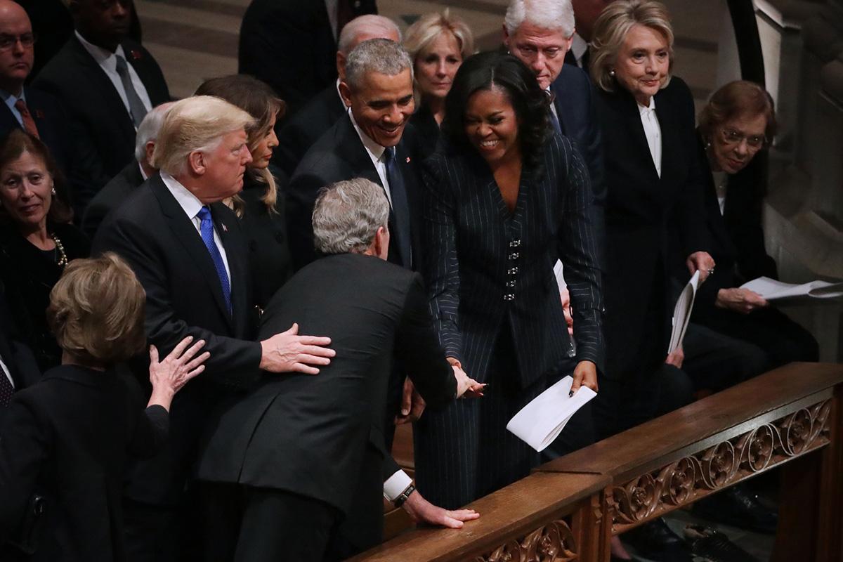 Former U.S. President George W. Bush (C) leans across President Donald Trump and first lady Melania Trump to greet fellow former president Barack Obama former first lady Michelle Obama on Dec. 5, 2018, in Washington.