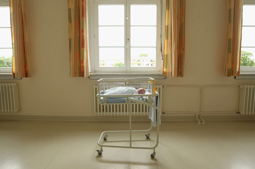 A 4-day-old newborn baby, who has been placed under a window by the photographer, lies in a baby bed in the maternity ward of a hospital (a spokesperson for the hospital asked that the hospital not be named) on August 12, 2011 in a city in the east German state of Brandenburg, Germany. According to data released by Eurostat last week Germany, with 8.3 births per 1,000 people, has the lowest birth rate in all of Europe. Eastern Germany, which not only suffers from a low birth rate, also has a declining population due to young people moving away because of high unemployment in the region. Europe as a whole suffers from a low birth rate and a growing elderly population. (Photo by Sean Gallup/Getty Images)