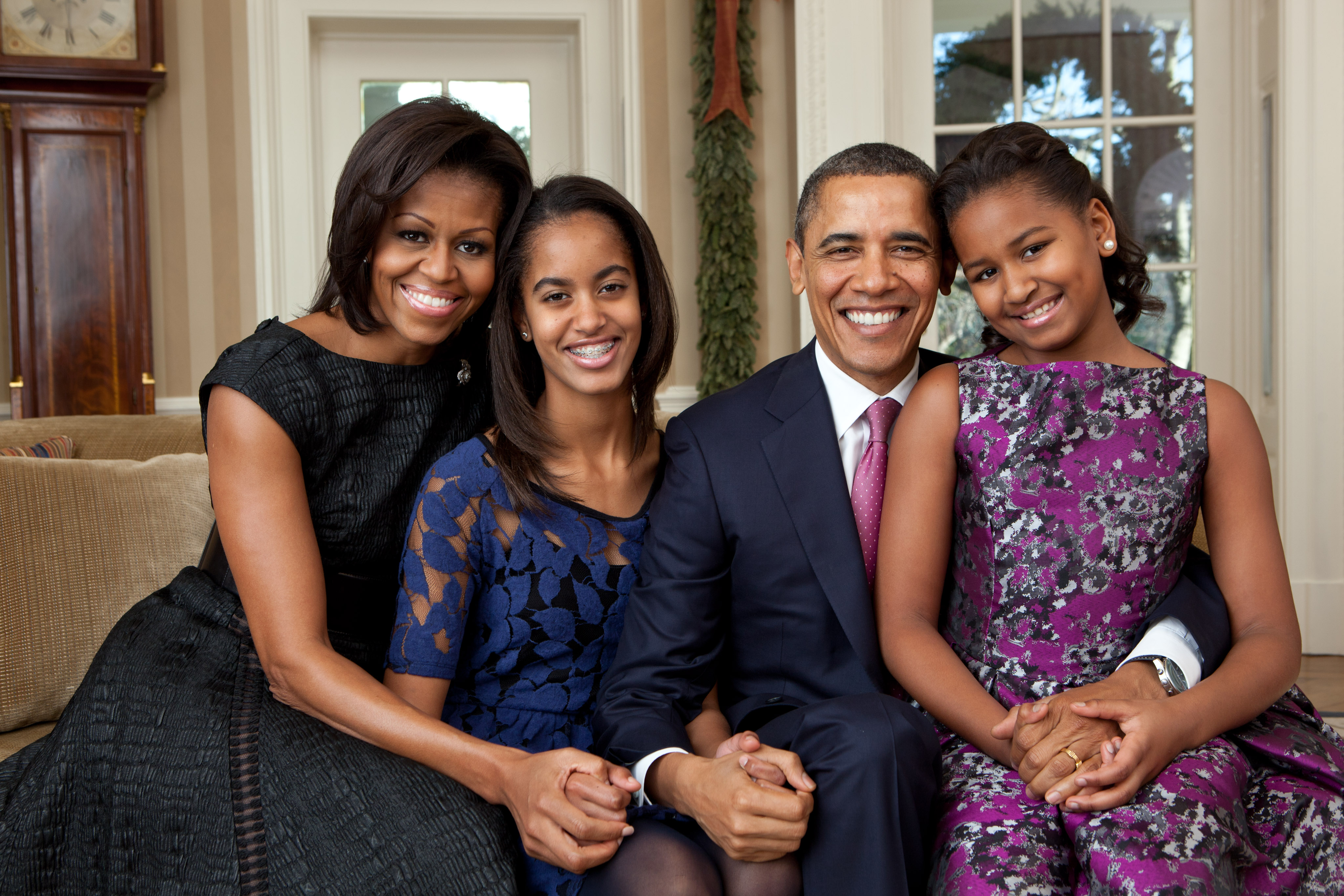 In this handout file photo provided by the White House, (L - R) First Lady Michelle Obama, Malia Obama, U.S. President Barack Obama and Sasha Obama, sit for a family portrait in the Oval Office on December 11, 2011 in Washington, D.C.