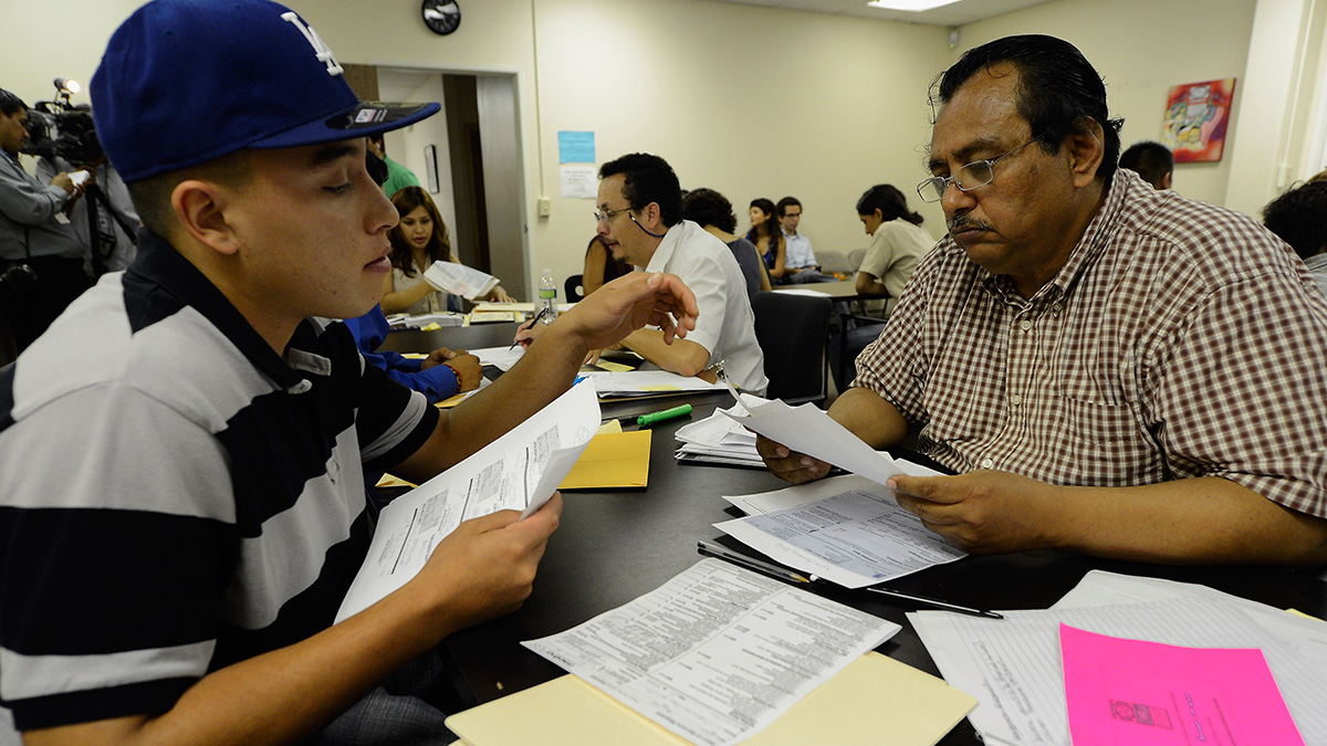 In this Aug. 15, 2012, file photo, Oscar Barrera-Gonzalez (left) receives help from volunteer Ivan Corpeno in filing up his application for Deferred Action for Childhood Arrivals program in Los Angeles.