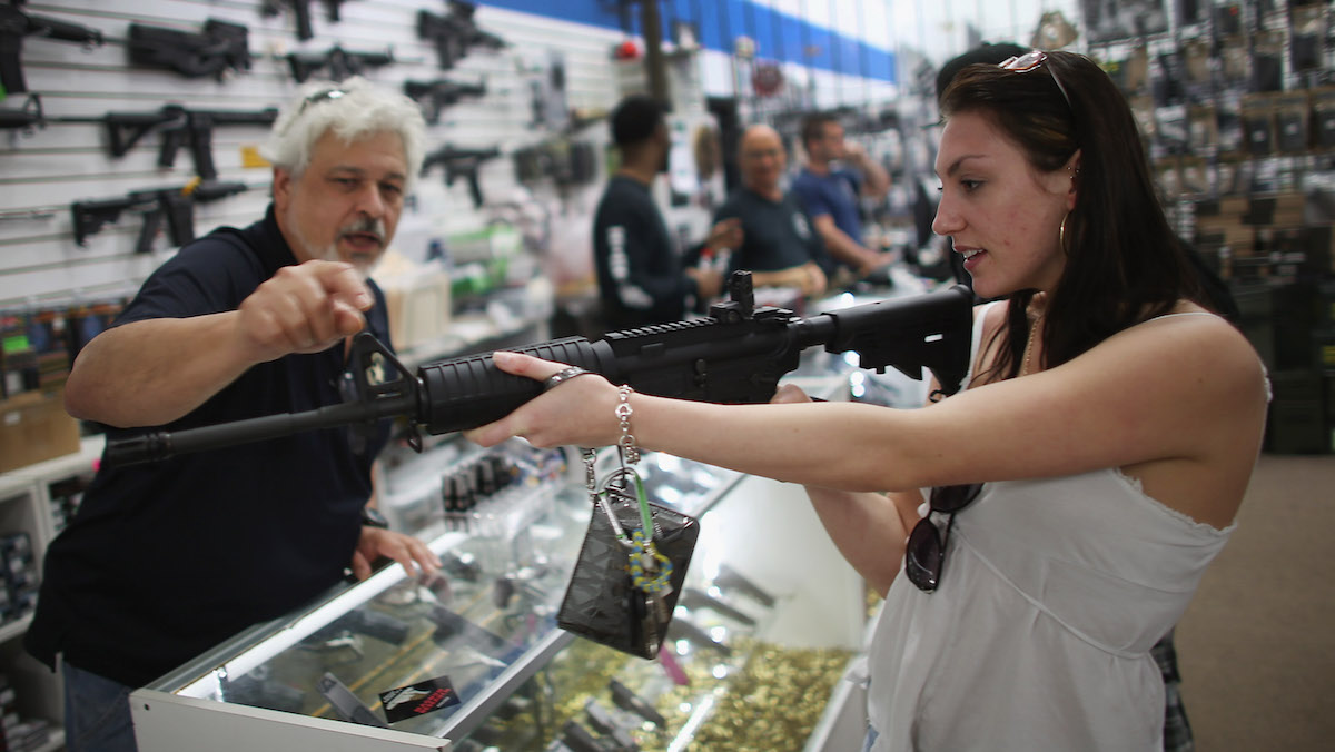In this file photo, a co-owner of the National Armory gun store, helps Cristiana Verro consider fire arms on April 11, 2013 in Pompano Beach, Florida.
