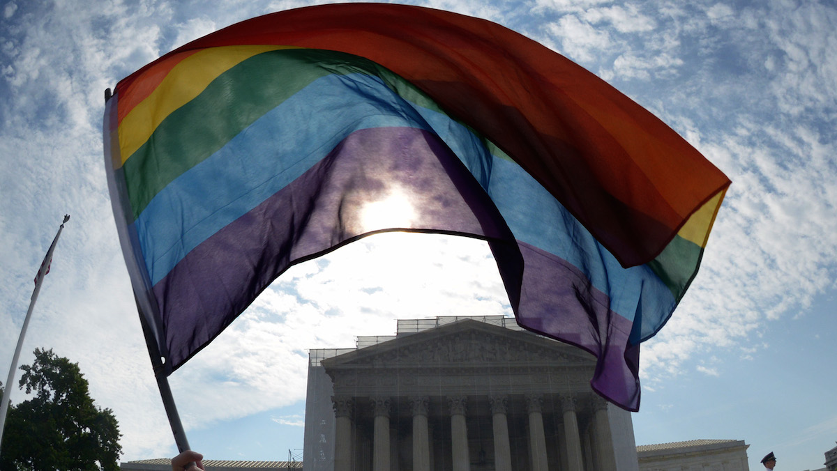 Vin Testa, of the District, waves a rainbow flag in front of the US Supreme Court, which is expected to hand down decisions on same sex marriage.