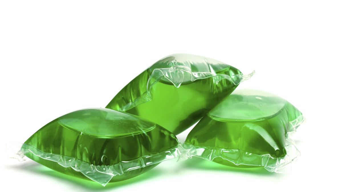 Three green laundry detergent capsules.