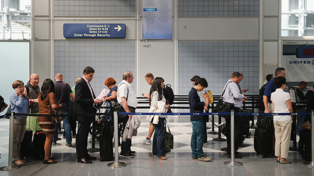 In this file photo, passengers wait in line to go through security screening at O'Hare International Airport's Terminal 1 shortly after the terminal was reopened on September 24, 2014 in Chicago, Illinois.