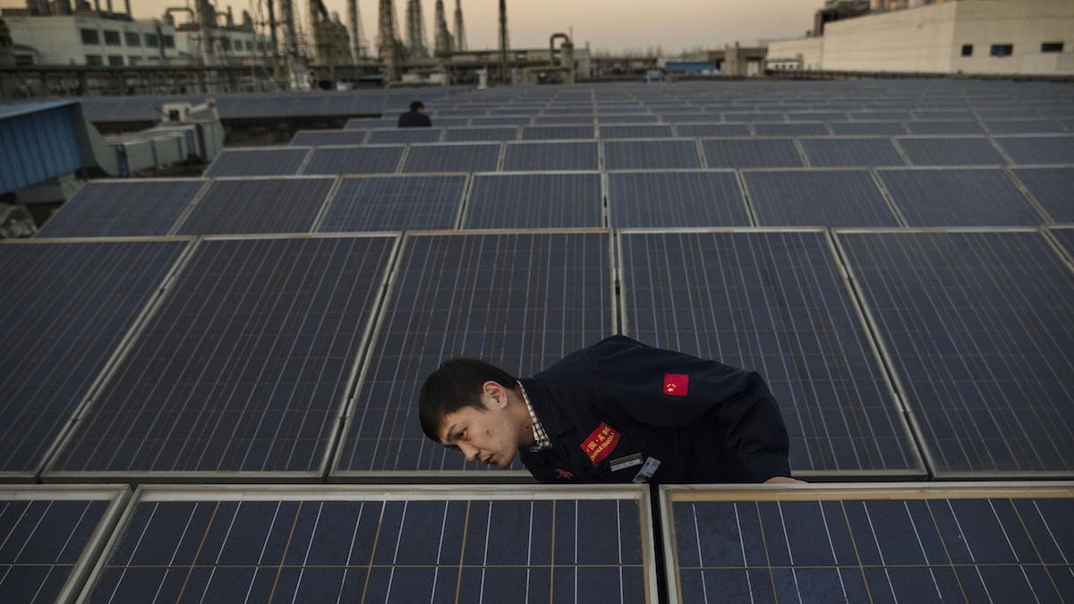 FILE- A manager from Yingli Solar checks a solar panel used to produce energy for lighting, on the roof at the company's headquarters on Dec. 4, 2014 in Baoding, Hebei Province. China is the largest energy consumer in the world with the main source of its electricity generated by coal, but in moves to reduce carbon emissions China is also setting records for installing solar panels and generating solar power.