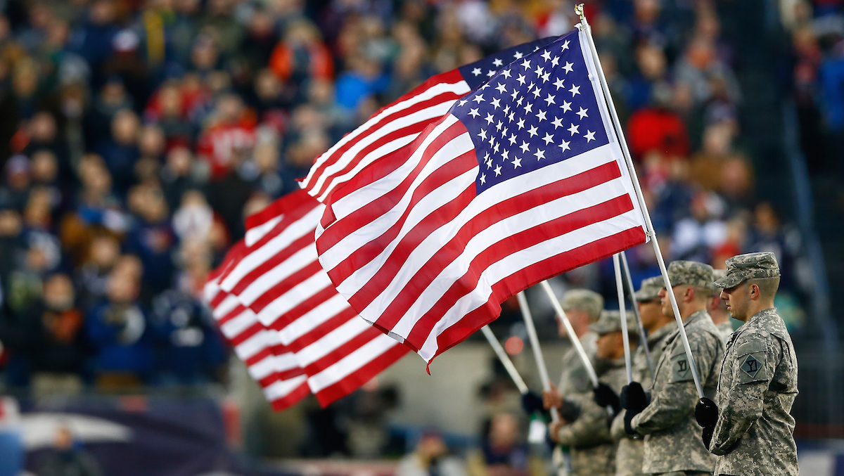 In this file photo, military members hold flags before the 2014 AFC Divisional Playoffs game between the New England Patriots and the Baltimore Ravens at Gillette Stadium on January 10, 2015 in Foxboro, Massachusetts.