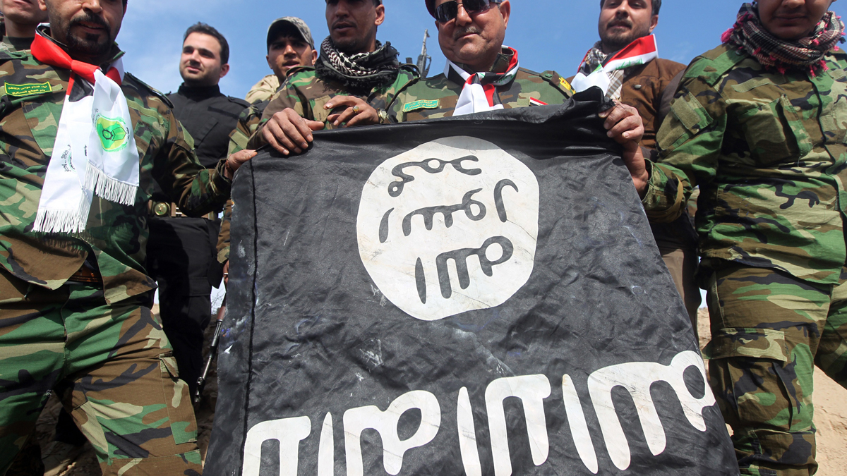 In this file photo, volunteer Shiite fighters who support the Iraqi government forces in the combat against the Islamic State (IS) group hold a black Islamist flag allegedly belonging to IS militants on February 24, 2015.