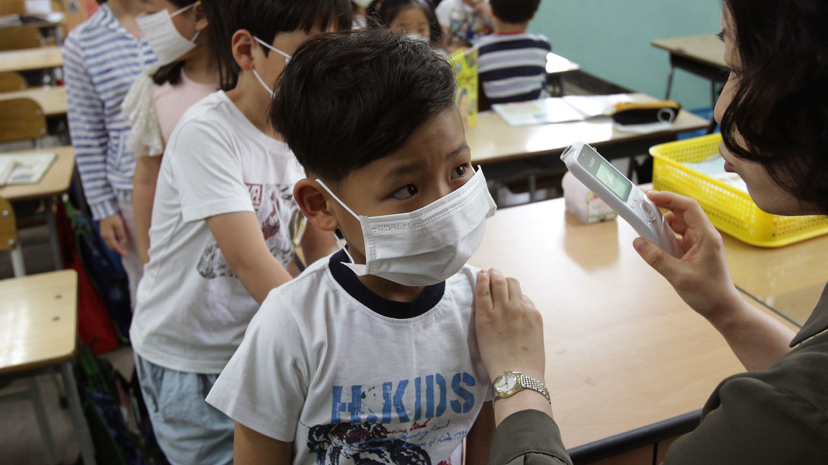 A teacher checks the temperature of a student as they wear masks as a precaution against the MERS virus at Midlong Elementary on June 9, 2015 in Seoul, South Korea. South Korea has reported 11 deaths related to the virus with 2,500 people quarantined and 1,800 schools closed. The virus is expected to continue to spread and make its way to the United States, according to experts.