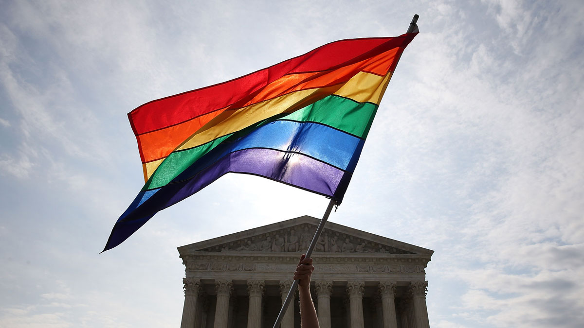A same-sex marriage supporter waves a flag in front of the Supreme Court Building June 25, 2015 in Washington, D.C.