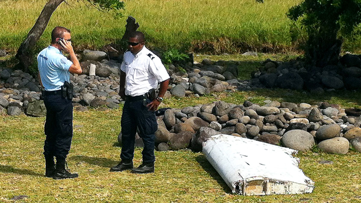 A policeman and a gendarme stand next to a piece of debris found in the coastal area of Saint-Andre de la Reunion, in the east of the French Indian Ocean island of La Reunion, on July 29, 2015. Officials said Wednesday, Aug. 5, 2015, the part came from  Malaysia Airlines Flight 370.