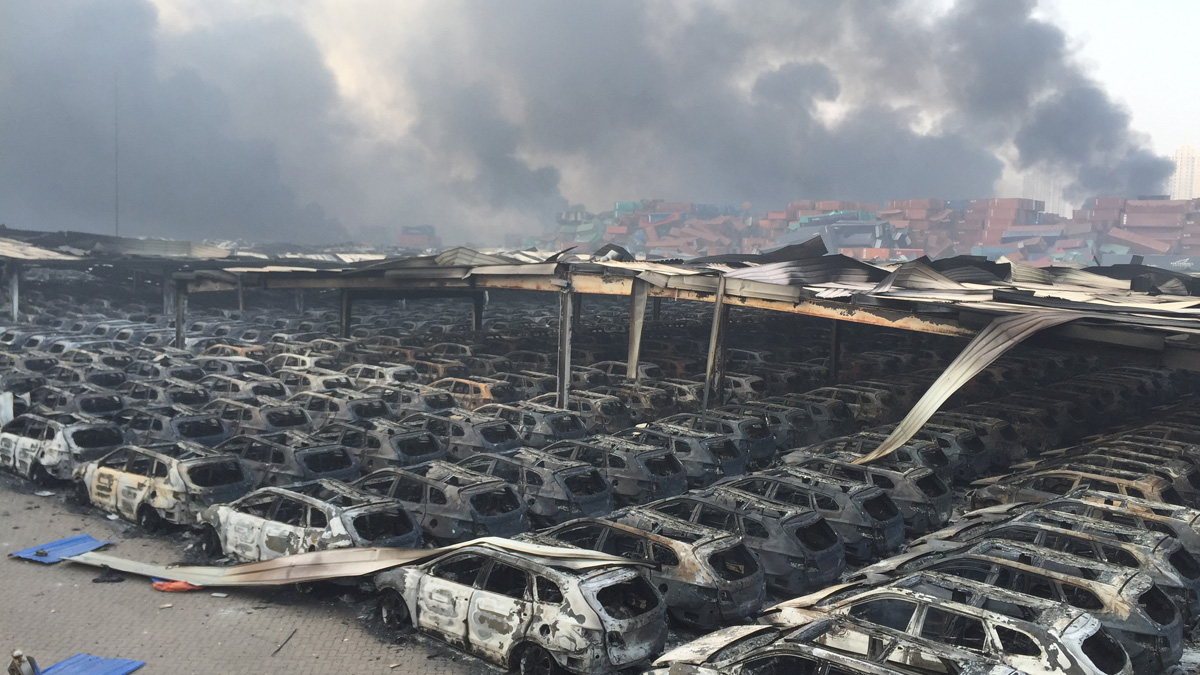 Burnt car debris continues to burn following the explosion of a warehouse in Binhai New Area on August 13, 2015 in Tianjin, China.