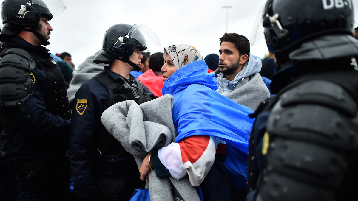 Slovenian police help migrants at the Trnovec border crossing after being stuck in cold and wet weather on October 19, 2015 in Trnovec ,Croatia. Slovenian authorities closed the border after reaching their daily quota, leaving over 1000 migrants stranded as hundreds more continue to arrive.