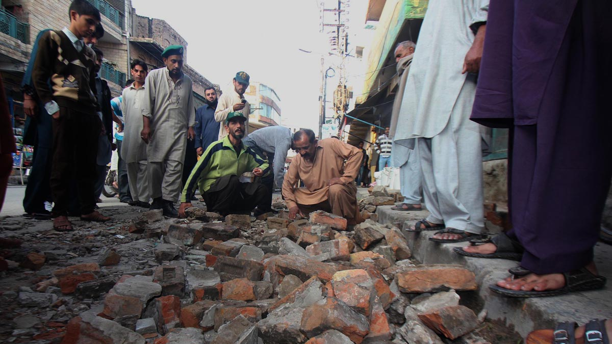 PAKISTAN, LAHORE, PUNJAB - 2015/10/27: People looking at the fallen debris after the powerful earthquake struck Rawalpindi. At least 350 people were killed and over 2,000 others injured when an earthquake measuring 8.1 on the Richter scale hit Pakistan on Monday, local media and MET officials said. (Photo by Rana Sajid Hussain/Pacific Press/LightRocket via Getty Images)
