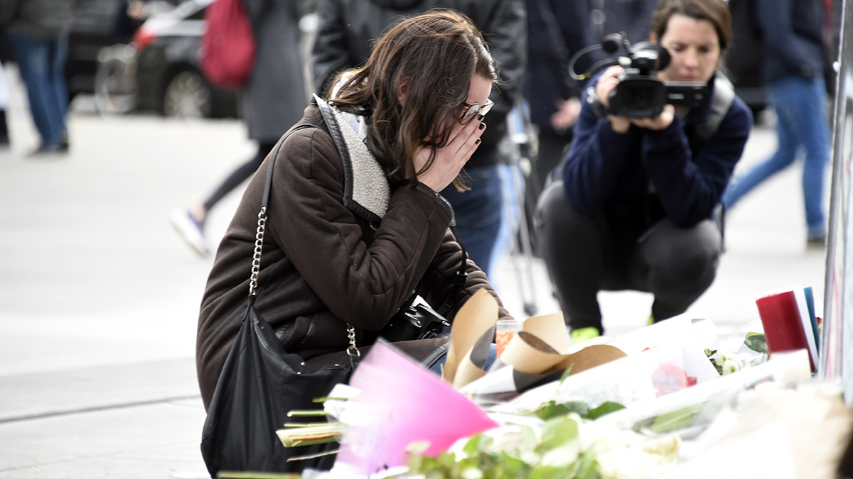 A young woman reacts in front of flowers and candles placed at the monument at the Place de la Republique in Paris on Nov. 14, 2015, following a series of coordinated attacks in and around Paris late Nov. 13, which left more than 120 people dead.