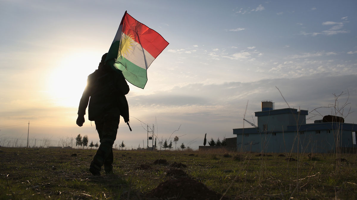 This November 16, 2015, file photo shows a Peshmerga soldier walking to place a Kurdish flag near the frontline with ISIS in Sinjar, Iraq.