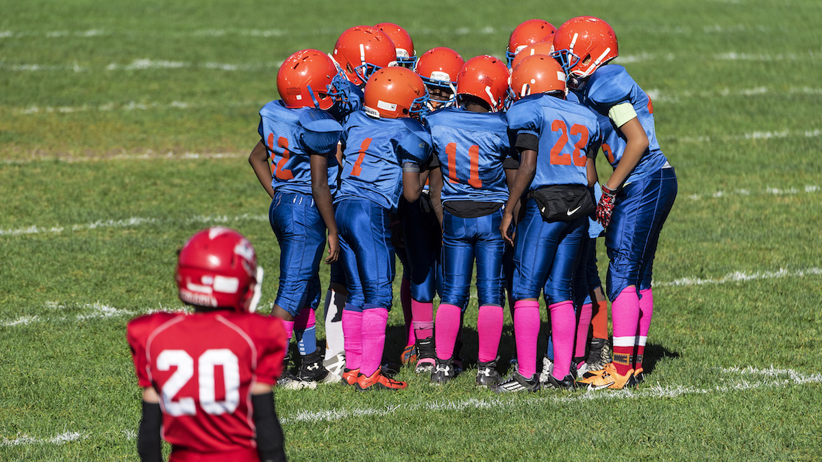 An undated file photo of young boys in the huddle during a Pop Warner football game.