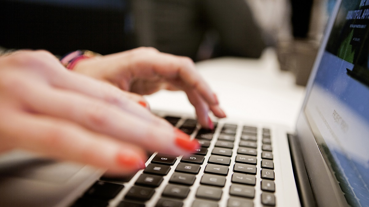 Cropped image of businesswoman using laptop in office