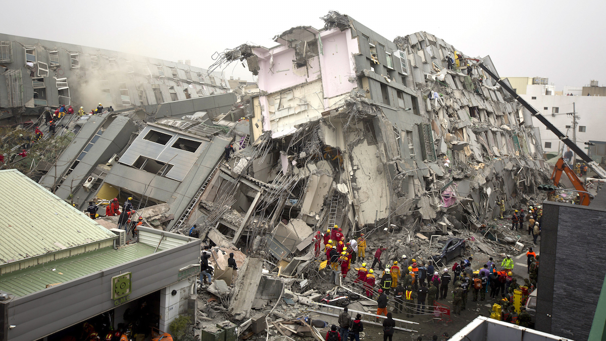 Rescue personnel search for survivors at the site of a collapsed building on February 6, 2016 in Tainan, Taiwan. A magnitude 6.4 earthquake hit southern Taiwan early Saturday, toppling several buildings and killing at least two people in Tainan, according to local news reports.  (Photo by Ashley Pon/Getty Images)