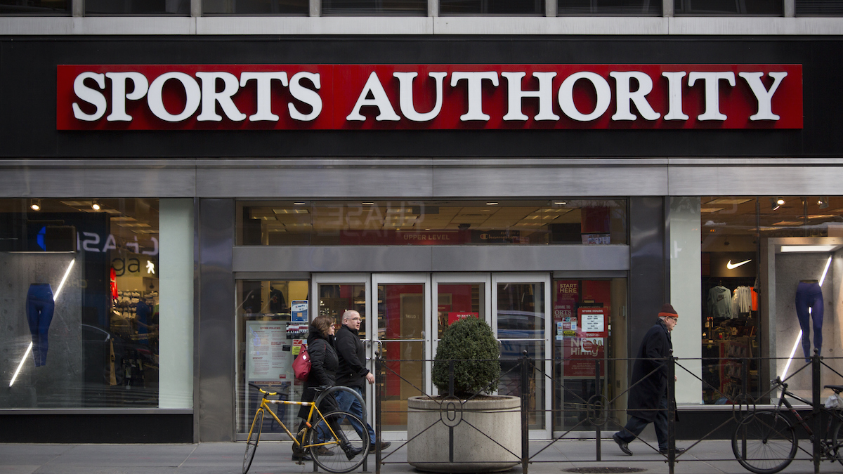 Pedestrians walk past a Sports Authority Inc. store in New York, U.S., on Saturday, Feb. 6, 2016. Sports Authority, once the biggest sporting-goods chain in the U.S., is preparing to file for bankruptcy.