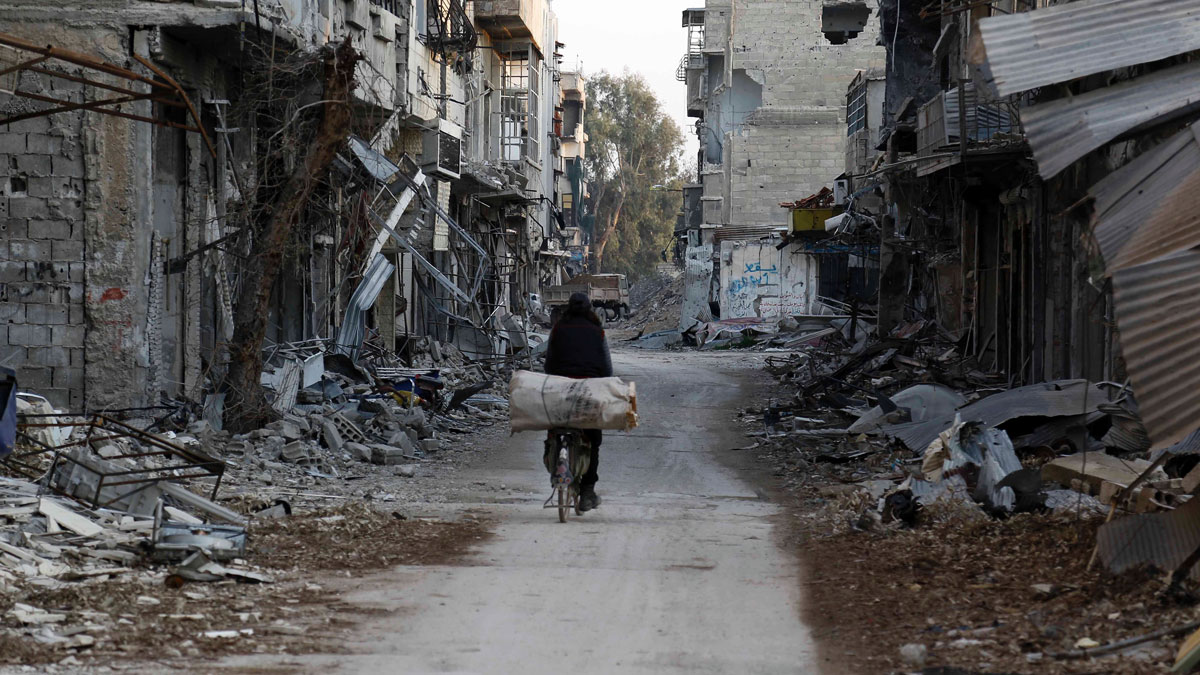 File Photo: Syrian man rides his bike along a street damaged by shelling in the neighborhood of Jobar, on the eastern outskirts of the capital Damascus, on Feb. 24, 2016.