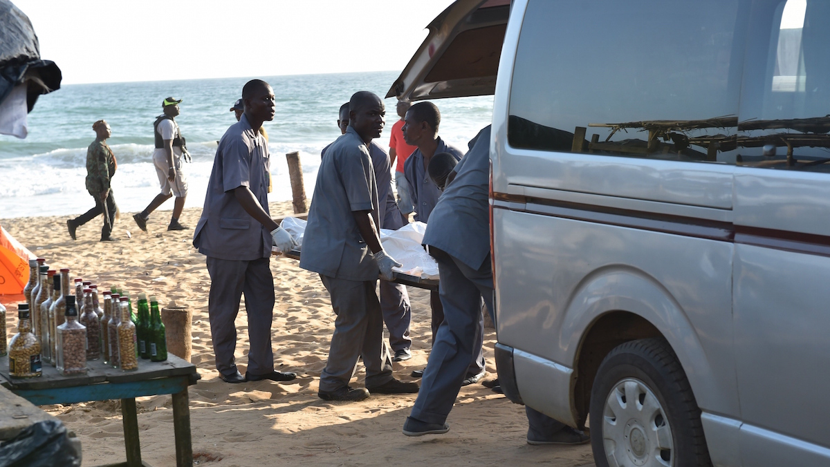 Employees load a body into a van after heavily-armed gunmen opened fire in the Ivory Coast resort town of Grand-Bassam, leaving bodies strewn on the beach, killing at least five people. The assailants, who were