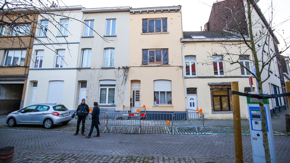 People stand on March 16, 2016 outside the sealed house of the apartment where a shooting took place the day before during an anti-terror operation in the rue du Dries-Driesstraat in Forest-Vorst, Brussels.