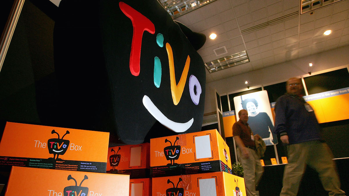 FILE- A display of TiVo boxes at the 2005 Consumer Electronics Show January 6, 2005 in Las Vegas, Nevada. The Digital TV listing company Rovi is buying the DVR maker in a cash-and-stock deal valued at about $1.1 billion.