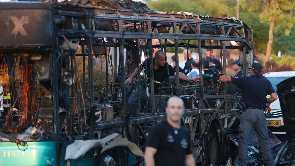 Israeli police check a burnt-out bus following in Jerusalem on April 18, 2016.