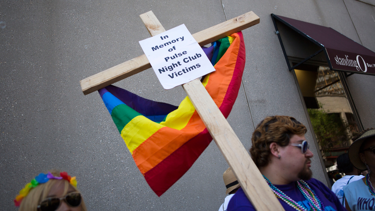 Austin Ellis, a member of Metropolitan Community Church, carries a cross with a sign in memory of the victims of the Pulse nightclub shooting as he marches in the 2016 Gay Pride Parade on June 12, 2016, in Philadelphia, Pennsylvania.