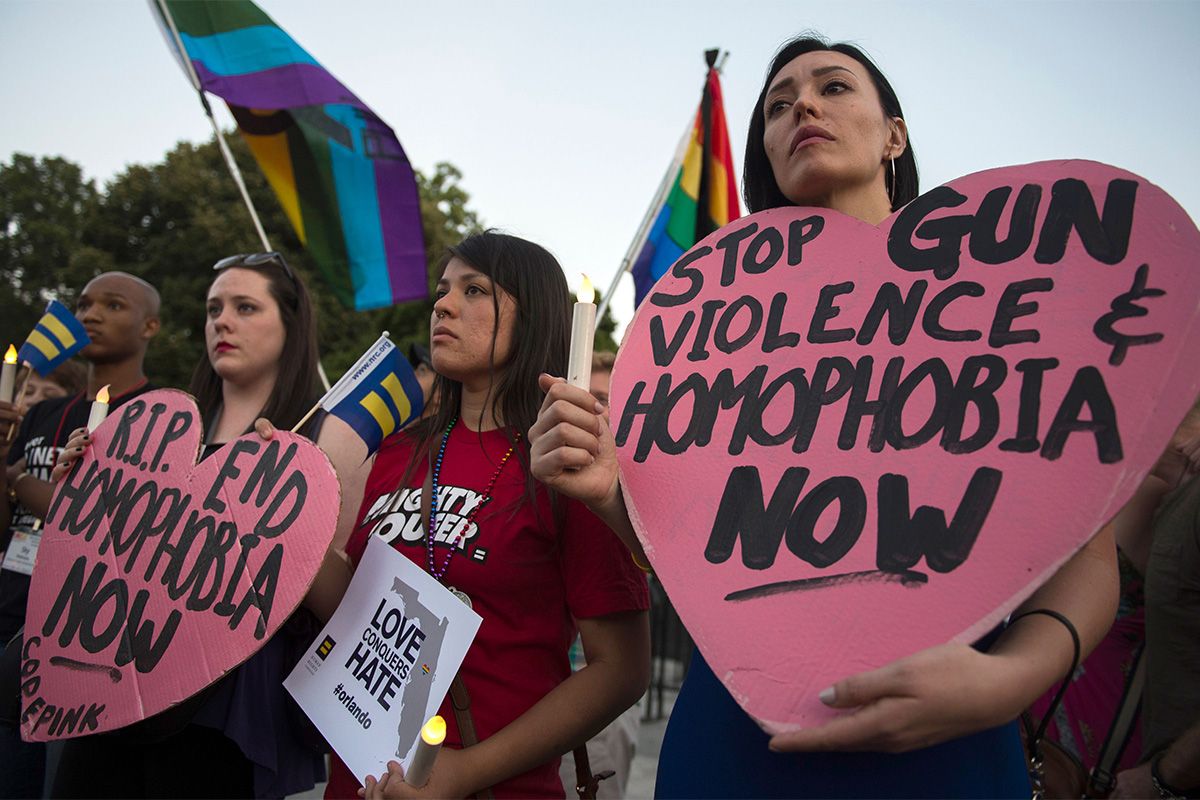 TOPSHOT - Mourners hold up signs during a vigil in Washington, DC on June 12, 2016, in reaction to the mass shooting at a gay nightclub in Orlando, Florida. Fifty people died when a gunman allegedly inspired by the Islamic State group opened fire inside a gay nightclub in Florida, in the worst terror attack on US soil since September 11, 2001. / AFP / Andrew Caballero-Reynolds (Photo credit should read ANDREW CABALLERO-REYNOLDS/AFP/Getty Images)