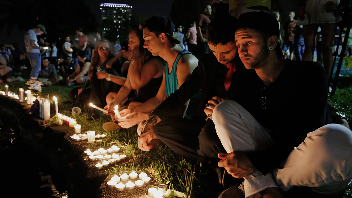 Johnpaul Vazquez, right, and his boyfriend Yazan Sale, sit by Lake Eola, in downtown Orlando. Fifty people were killed and more than 50 others injured in a mass shooting at Pulse nightclub in Orlando, Florida.