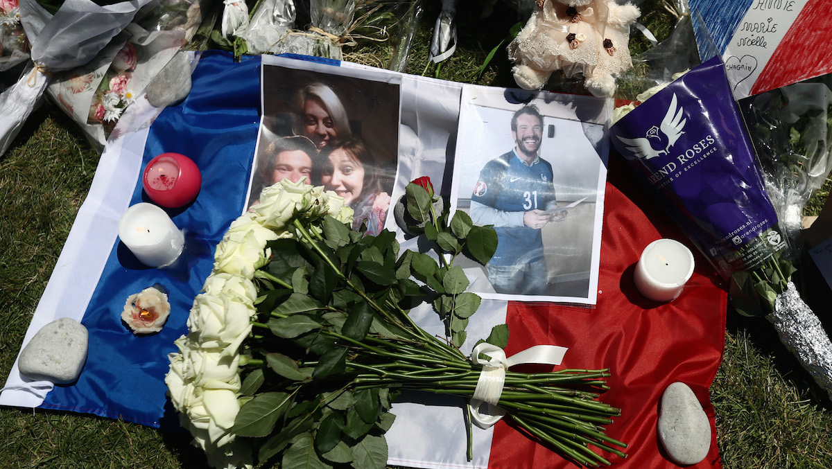 Tributes and flowers are left with a French flag on the Promenade des Anglais on July 16, 2016 in Nice, France. Five people believed to be linked to the man who killed 84 people in Nice are in police custody according to a statement by the Paris prosecutor's office after a French-Tunisian attacker killed 84 people as he drove a lorry through crowds who had gathered to watch a firework display during Bastille Day Celebrations. The attacker then opened fire on people in the crowd before being shot dead by police.