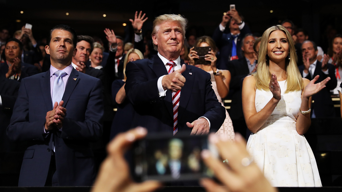 In this July 20, 2016, photo, Donald Trump gives a thumbs up as Donald Trump Jr. and Ivanka Trump stand and cheer for Eric Trump as he delivers his speech during the third day of the Republican National Convention in Cleveland, Ohio.