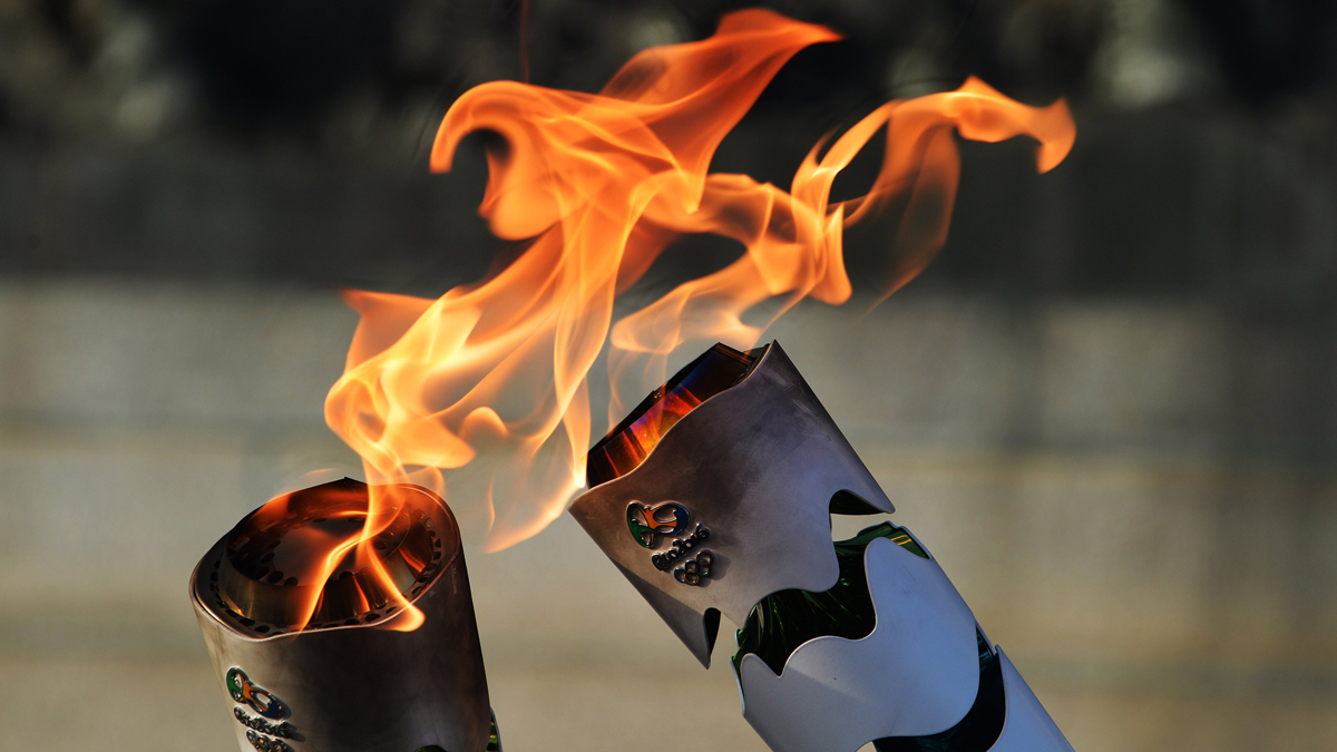 In this file photo, Brazilian residents pass the Olympic torch at Independence Park upon the flame's arrival in Sao Paulo, Brazil, on July 24, 2016.