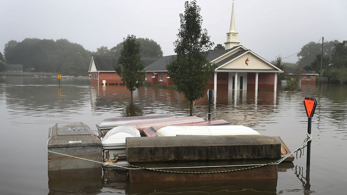 Caskets are seen floating in flood waters near a cemetery on August 17, 2016 in Gonzales, Louisiana. Starting last week the state was overwhelmed with flood water causing at least 13 deaths and thousands of homes damaged by the flood waters.