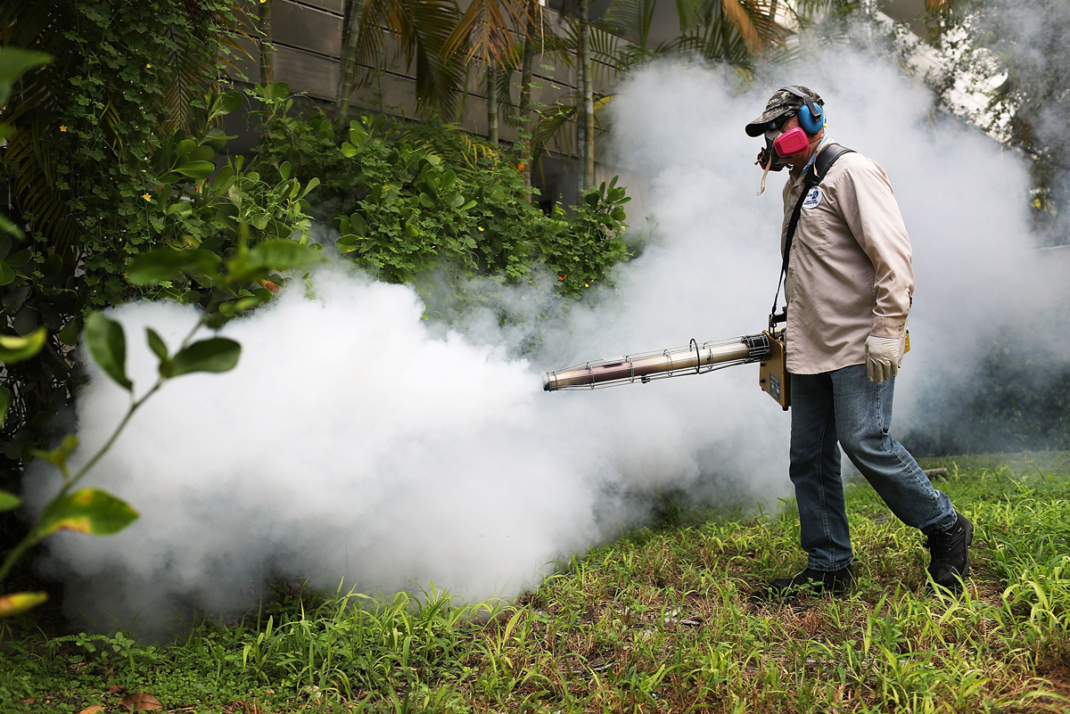 Carlos Varas, a Miami-Dade County mosquito control inspector, uses a Golden Eagle blower to spray pesticide to kill mosquitos in the Miami Beach neighborhood as the county fights to control the Zika virus outbreak on Aug. 24, 2016, in Miami Beach, Florida. The number of locally transmitted cases in Wynwood and Miami Beach has reached 41.