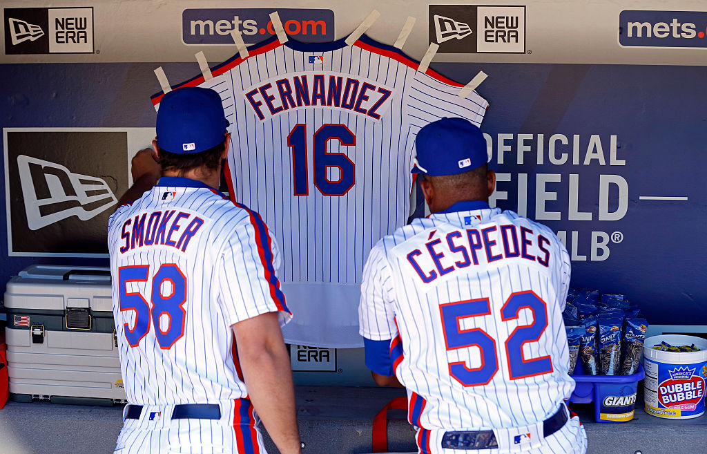 NEW YORK, NY - SEPTEMBER 25: Yoenis Cespedes #52 of the New York Mets and Josh Smoker #58 of the New York Mets hang a jersey for Jose Fernandez of the Miami Marlins in their dugout prior to taking on the Philadelphia Phillies at Citi Field on September 25, 2016 in the Flushing neighborhood of the Queens borough of New York City. Fernandez died earlier in the day in a boating accident. (Photo by Adam Hunger/Getty Images)