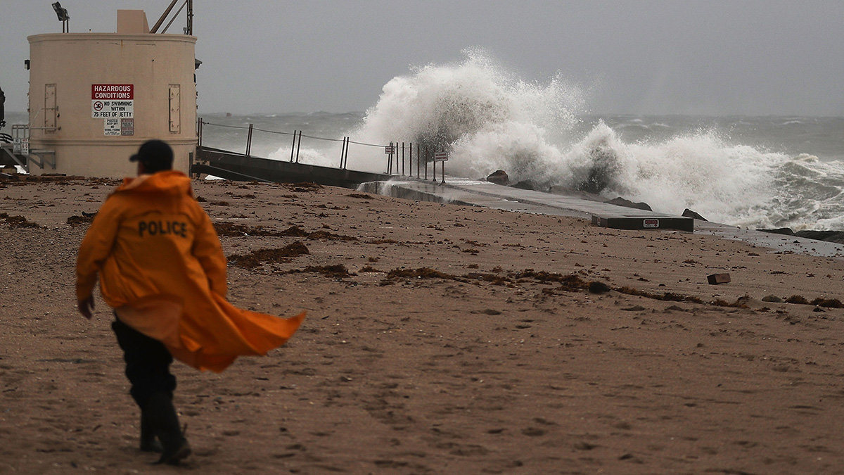 A police officer walks along the beach as waves crash ashore as Hurricane Matthew approaches the area on October 6, 2016, in Singer Island, Florida.