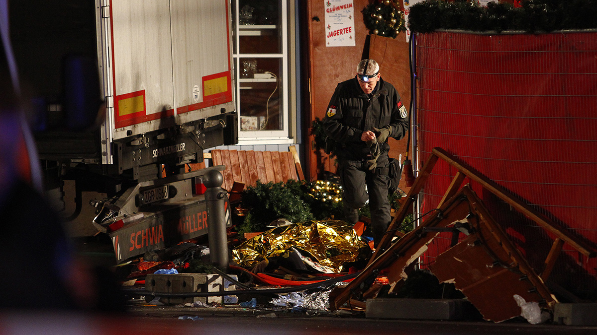 Security and rescue workers inspect a lorry truck after it was crashed through a Christmas market. Authorities have not yet confirmed the nature of the incident.