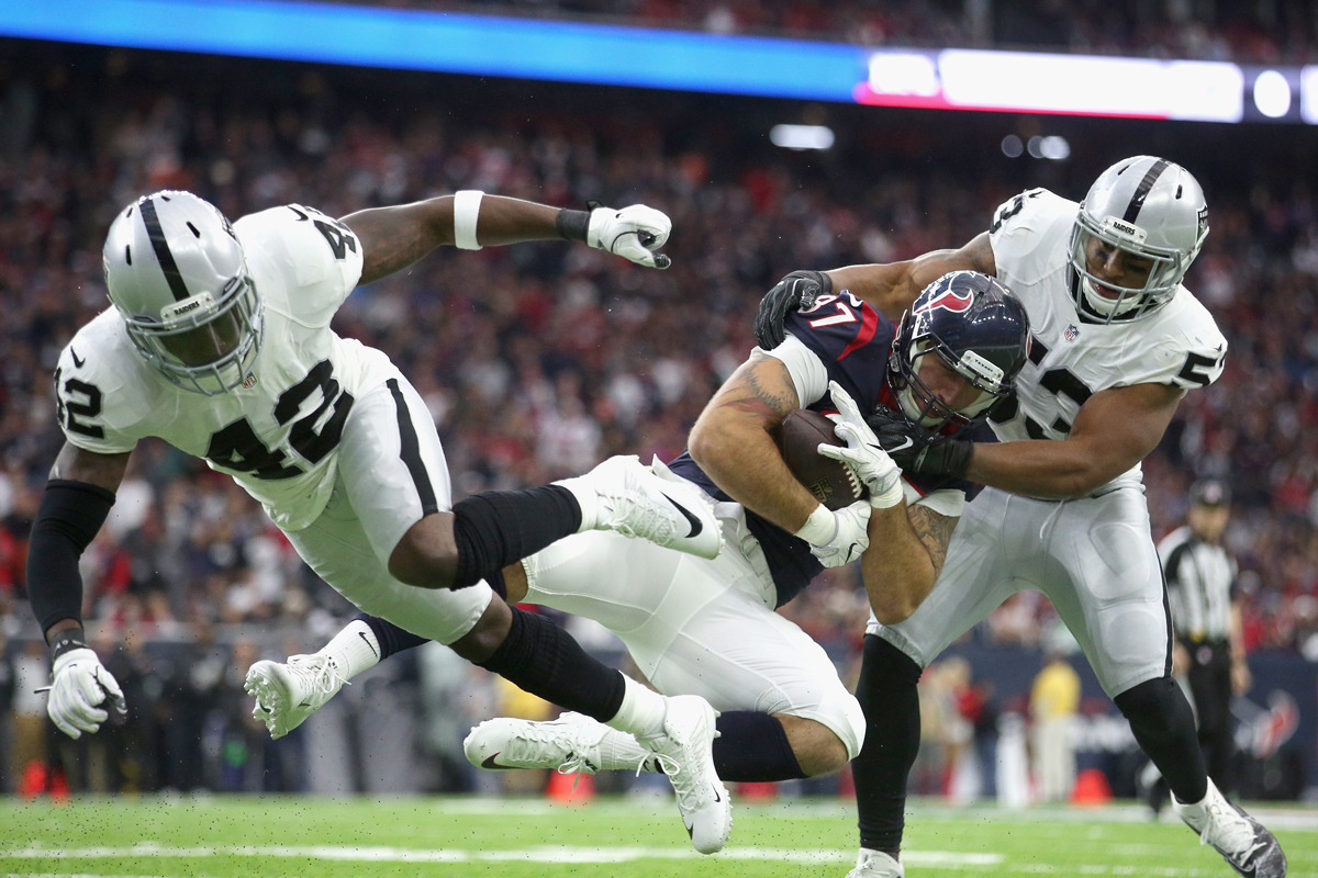 C.J. Fiedorowicz #87 of the Houston Texans makes a catch against Karl Joseph #42 and Malcolm Smith #53 of the Oakland Raiders during the AFC Wild Card game at NRG Stadium on Jan. 7, 2017, in Houston, Texas. The Texans won 27-14.