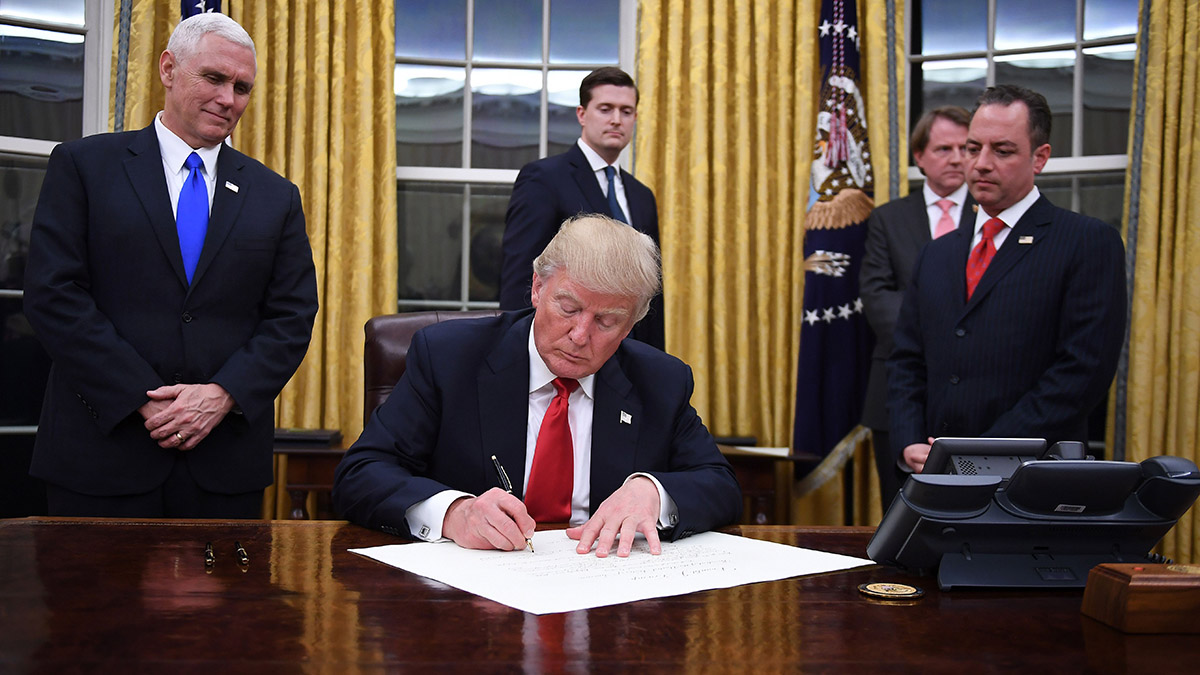 In this Jan. 20, 2017, file photo, President Donald Trump signs an executive order at the White House in Washington, D.C.