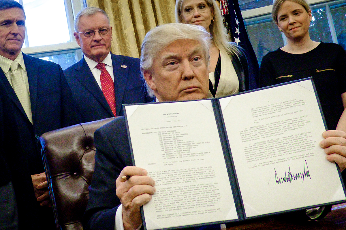 File Photo—President Donald Trump holds up one of the executive actions that he signed in the Oval Office on Jan. 28, 2017 in Washington, D.C.