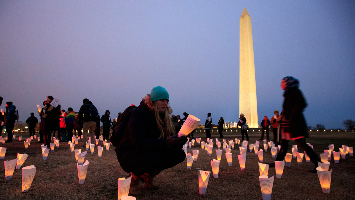 Protestors write messages directed toward President Donald Trump on lanterns near the Washington Monument, February 3, 2017, in Washington, DC. The protest is aimed at President Trump's travel ban policy.